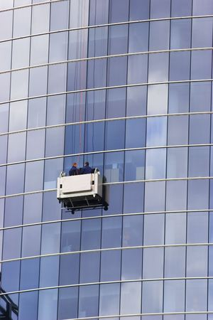 business life line: Two window cleaners in a gondola cleaning the windows of a corporate office skyscraper.