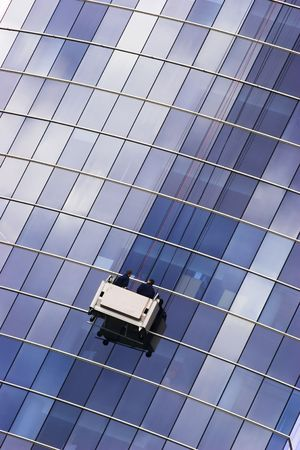 Two window cleaners in a gondola cleaning the windows of a corporate office skyscraper. Stock Photo - 940728