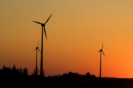 Three windturbines against dramatic sunset producing environment friendly energy photo
