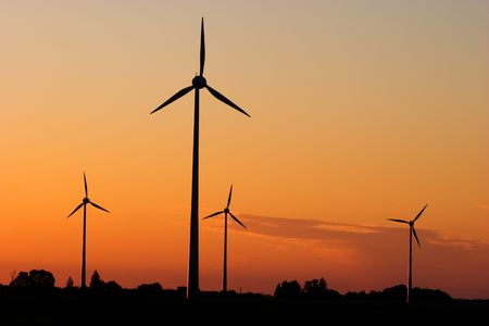 Four windturbines against dramatic sunset producing environment friendly energy Stock Photo