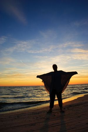 Sunset silhouette of young woman at coast of sea Stock Photo - 1243420