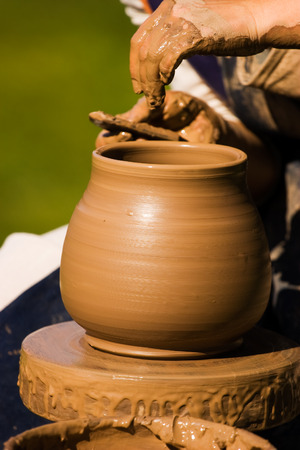 Potters hands creating a traditional clay vase on the turning wheel photo