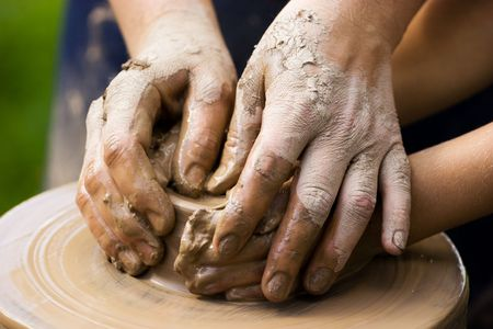 potter: A potters hands guiding a child hands to help him to work with the ceramic wheel
