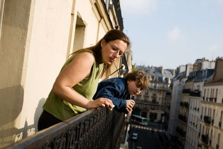 Mother and her son on balcony looking at city life.  photo