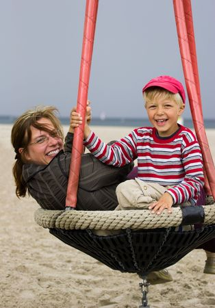 Mother and her son in beach playground. Windy summer day. photo