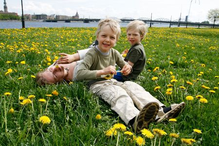 Mother and her sons in meadow with dandelions. Riga city in foreground. photo