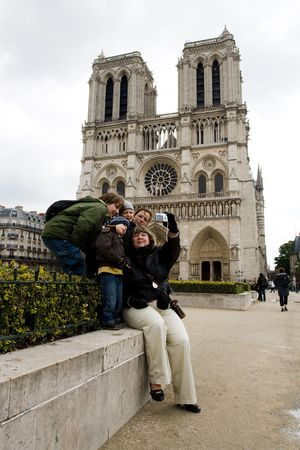 Group of tourists, members of one  taking self portrait at the famous CathÂŽdrale Notre-Dame de Paris photo