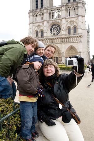 familia en la iglesia: Grupo de turistas, miembros de una familia teniendo autorretrato en el famoso Cath�drale Notre-Dame de Paris  Foto de archivo