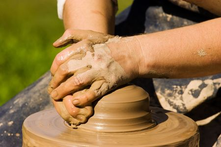 Potters hands starting to make new ceramic object photo