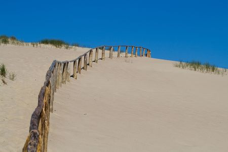 Wooden fence in sand dunes. Curonian Spit is on the UNESCOs World Heritage List in Lithuania photo