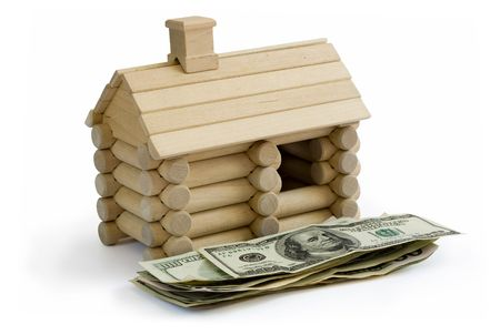 Miniature Log House building model and money dollar bills in foreground photo
