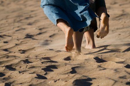 Barefoot legs on the sand beach. photo