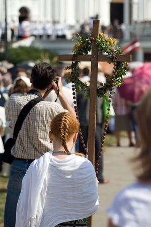 congregate: Young woman carrying cross through crowd at Day of the Assumption of Mary (15th August) Aglona, Latvia. Stock Photo