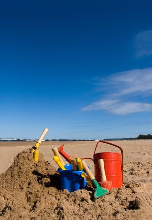 Red watering can, plastic blue bucket and other beach toys in the sandy seashore photo