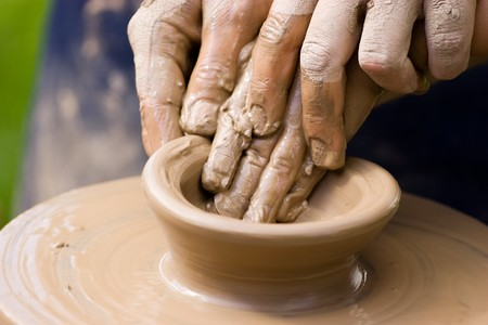 A potters hands guiding a child hands to help him to work with the ceramic wheel photo