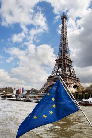 View at Eiffel tower across the Seine River from boat. European Union flag in front. photo