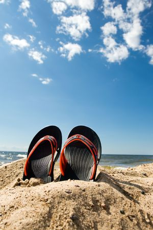 Pair of plastic beach slippers at the seashore photo