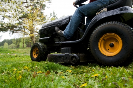 Worker mowing with black riding lawn mower Stock Photo