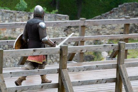 swordfight: CESIS, LATVIA, June 7, 2009: Knight before swordfight on wooden bridge during  the medieval festival �Livonia. 1378. Wenden�. Rainy day.