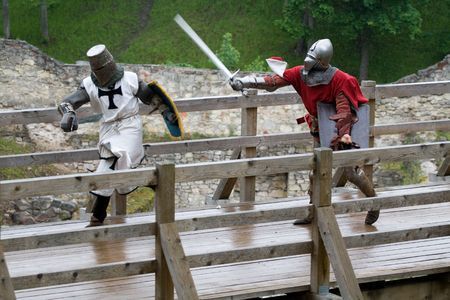 CESIS, LATVIA, June 7, 2009: Knight swordfight on wooden bridge during  the medieval festival ÒLivonia. 1378. WendenÓ. Rainy day. Stock Photo - 5014212