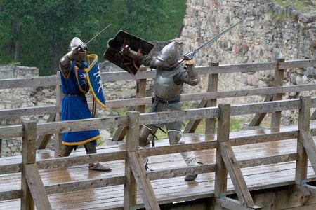 swordfight: CESIS, LATVIA, June 7, 2009: Knight swordfight on wooden bridge during  the medieval festival ÒLivonia. 1378. WendenÓ. Rainy day. Stock Photo