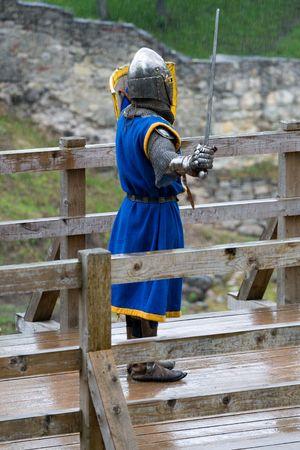 swordfight: CESIS, LATVIA, June 7, 2009: Knight swordfight on wooden bridge during  the medieval festival �Livonia. 1378. Wenden�. Rainy day.