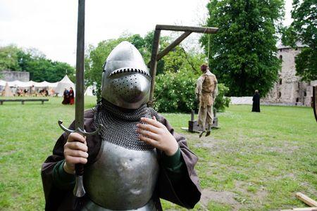 ahorcado: Caballero medieval y del cuerpo muerto colgando de horca en el fondo