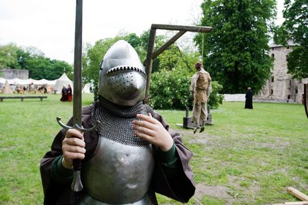 noose: Medieval knight and dead body hanging from gallows in background