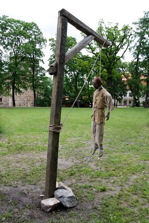 Manikin of dead man hanging from wooden gallows photo
