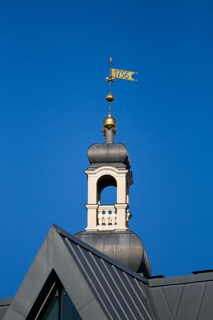 weathervane: Small turret with metalic weather vane of Riga city hall against blue sky