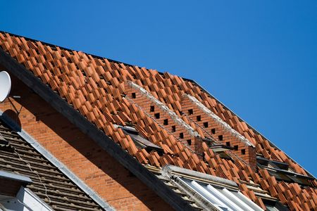 Red tile roof repair or construction work in progress photo