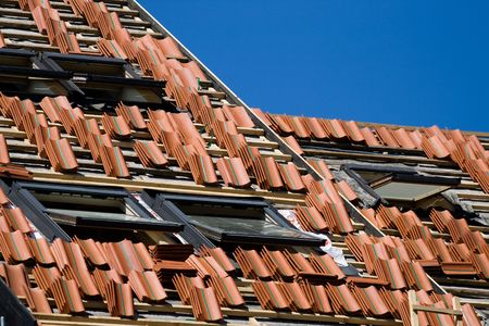 roof work: Red tile roof repair or construction work in progress