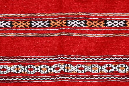 ethnographical: Red ethnographical handmade blanket with color pattern.