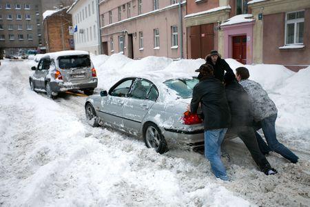 RIGA - 2 februari: Mensen duwen stuck auto in besneeuwde straat na zware sneeuwval in Riga, Letland, 2 februari 2010 het is extreem koude en besneeuwde winter in Europa (2009-2010).