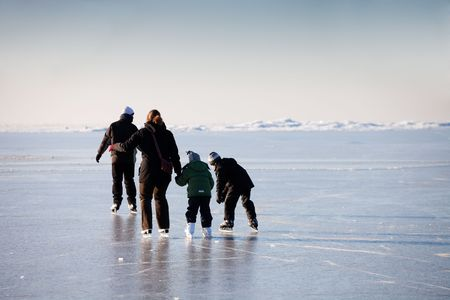 Family ice skating in natural rink frozen sea Stock Photo