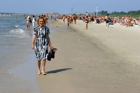 latvia girls: LIEPAJA, LATVIA - JULY 9: Old woman walking and relaxing in Crowded beach. Liepaja, Latvia, summer 2006