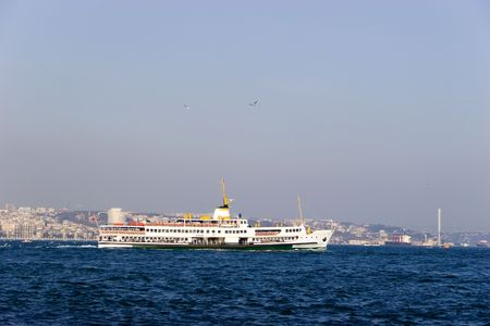 Passenger ferry sails between two continents, Europe and Asia in Bosporus Strait, Istanbul, Turkey photo