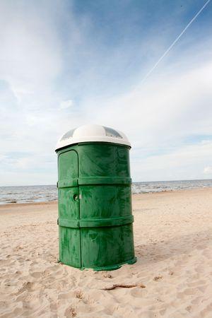 latrina: Verde toilette portatile in plastica nella spiaggia sabbiosa