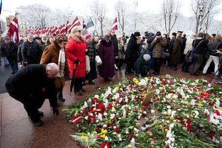 anti fascist: RIGA, LATVIA, MARCH 16, 2010: People lay dwn fowers at Freedom Monumunt. Commemoration of the Latvian Waffen SS unit or Legionnaires. The event is always drawing crowds of nationalist supporters and anti-fascist demonstrators. Many Latvians were forcibly