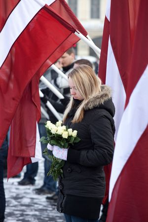 anti fascist: RIGA, LATVIA, MARCH 16, 2010: Young girl at Commemoration of the Latvian Waffen SS unit or Legionnaires.The event is always drawing crowds of nationalist supporters and anti-fascist demonstrators. Many Latvians were forcibly called to join the Latvian SS