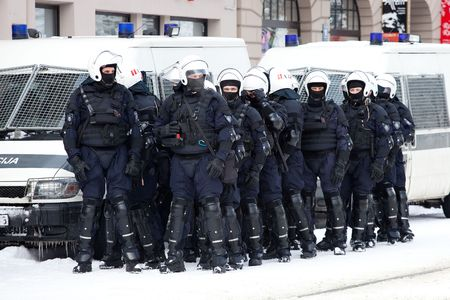 RIGA, LATVIA, MARCH 16, 2010: Riot police officers ready to prevent provocations at Commemoration of the Latvian Waffen SS unit or Legionnaires.The event is always drawing crowds of nationalist supporters and anti-fascist demonstrators. Many Latvians were Stock Photo - 6890411