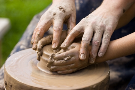 A potters hands guiding a child hands to help him to work with the ceramic wheel