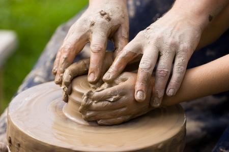 Een pottenbakkers handen begeleiden een kind handen om te helpen hem te werken met de keramische wiel