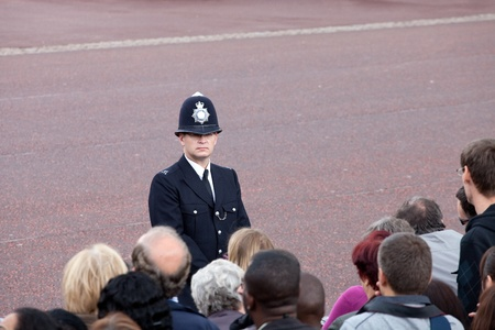 constable: LONDON - JUNE 11: British policeman observes the crowd of spectators during the Trooping the Color ceremony in London, England on June 11, 2011. Ceremony is performed by regiments on the occasion of the Queens Official Birthday