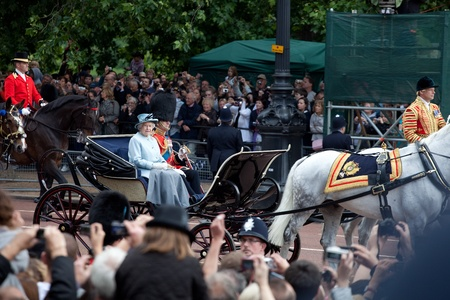 LONDON - JUNE 11: The Queen Elizabeth II and The Duke of Edinburgh leaves Trooping the Color ceremony trough streets crowded of spectators in London, England on June 11, 2011. Ceremony is performed by regiments on the occasion of the Queens Official Birt