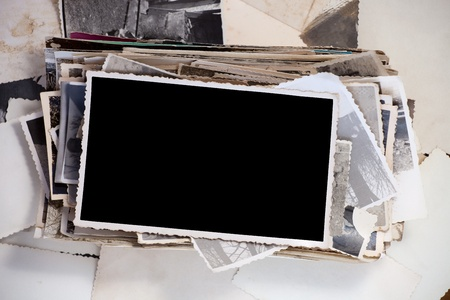 stacked: Stack of old photos with one blank photo for your image.
