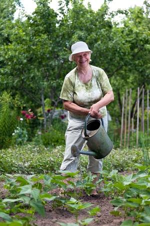Happy senior vrouw die in haar tuin