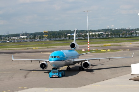 tow tractor: AMSTERDAM - JUNE 16: KLM Royal Dutch Airlines McDonnell Douglas MD-11 at Schiphol airport June 16, 2009 in Amsterdam, Netherlands. MD-11 is a three-engine medium to long range widebody jet airliner. Schiphol is the Netherlands main international airport a