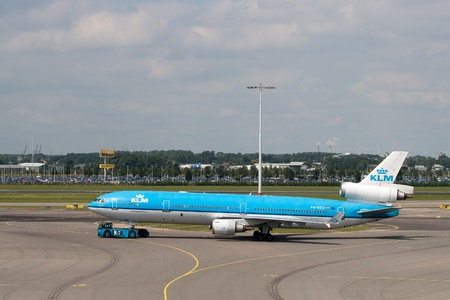 jetliner: AMSTERDAM - JUNE 16: KLM Royal Dutch Airlines McDonnell Douglas MD-11 at Schiphol airport June 16, 2009 in Amsterdam, Netherlands. MD-11 is a three-engine medium to long range widebody jet airliner. Schiphol is the Netherlands main international airport a