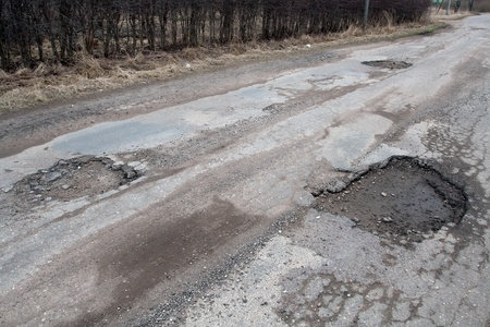 bad condition: Damaged asphalt pavement road with potholes caused by freeze and thaw cycle during winter.
